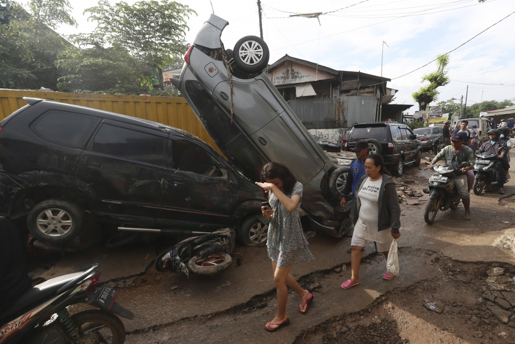 Residents walk near the wreckage of cars that were swept away by flood in Bekasi, West Java, Indonesia, Friday, Jan. 3, 2020.Severe flooding in greate...
