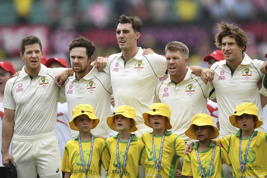 Australia players, from left, Tim Paine, Travis Head, Pat Cummins, David Warner and Joe Burns during the national anthems ahead of play on day one of ...