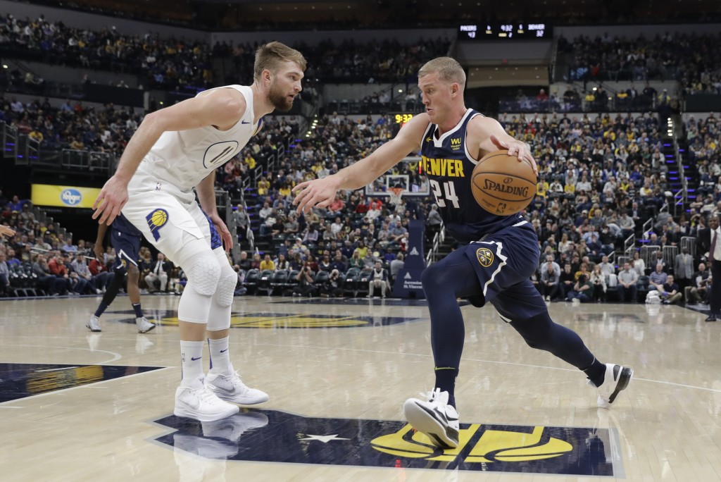 Denver Nuggets' Mason Plumlee (24) goes to the basket against Indiana Pacers' Domantas Sabonis (11) during the first half of an NBA basketball game Th...