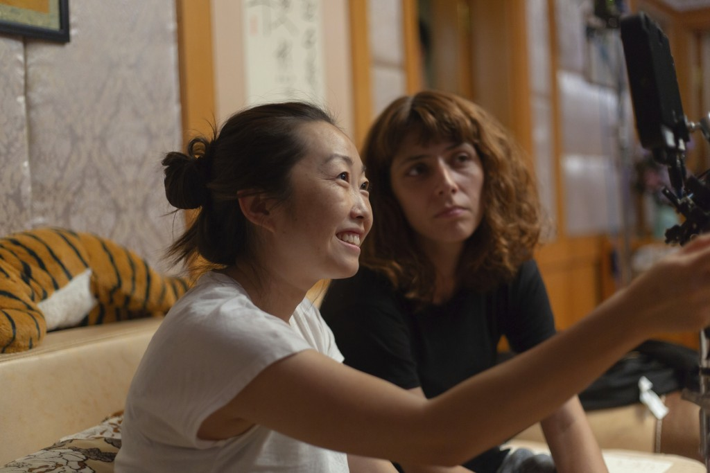 """This image released by A24 shows director Lulu Wang, left, on the set of """"The Farewell."""" Women directed 12 of 2019's top 100-grossing films in 2019, a..."""