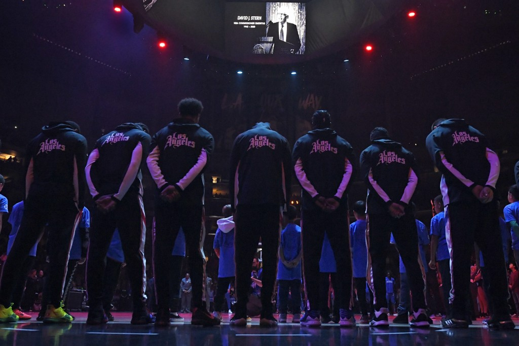 Members of the Los Angeles Clippers stand duringa a moment of silence Thursday, Jan. 2, 2020, in Los Angeles, prior to a basketball game against the D...