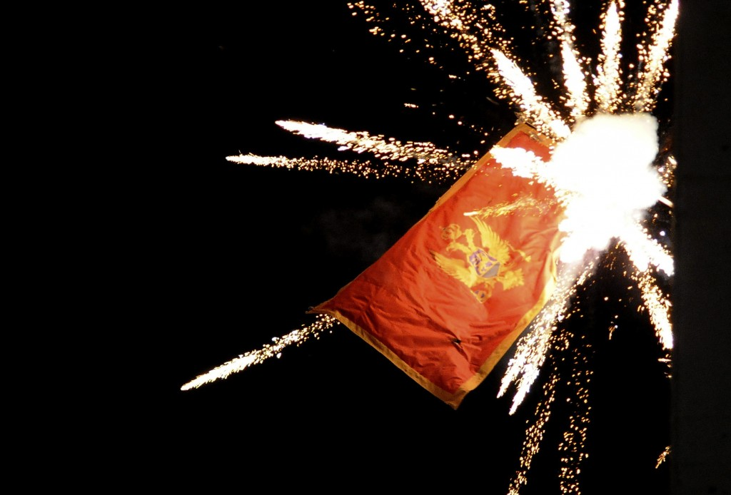The Montenegrin flag flying from the Montenegrin Embassy, is targeted with fireworks by Serbian ultra-nationalists during a protest against a religion...