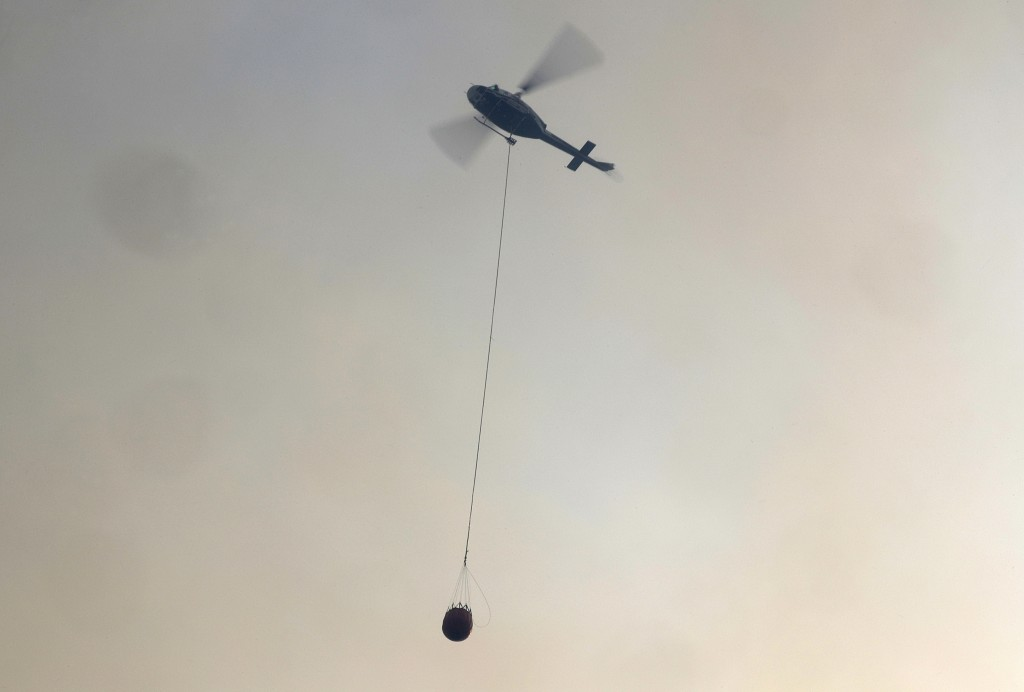 A helicopter carries a water bucket to douse a fire near Bendalong, Australia, Friday, Jan. 3, 2020. Navy ships plucked hundreds of people from beache...