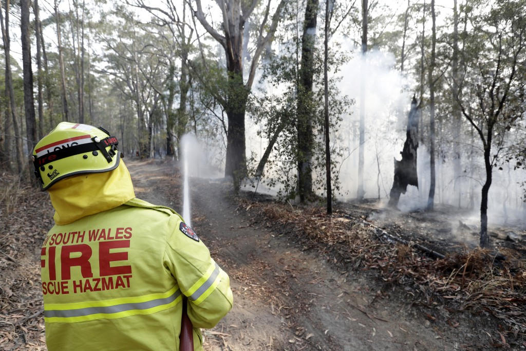 A firefighter battles a fire near Bendalong, Australia, Friday, Jan. 3, 2020. Navy ships plucked hundreds of people from beaches and tens of thousands...