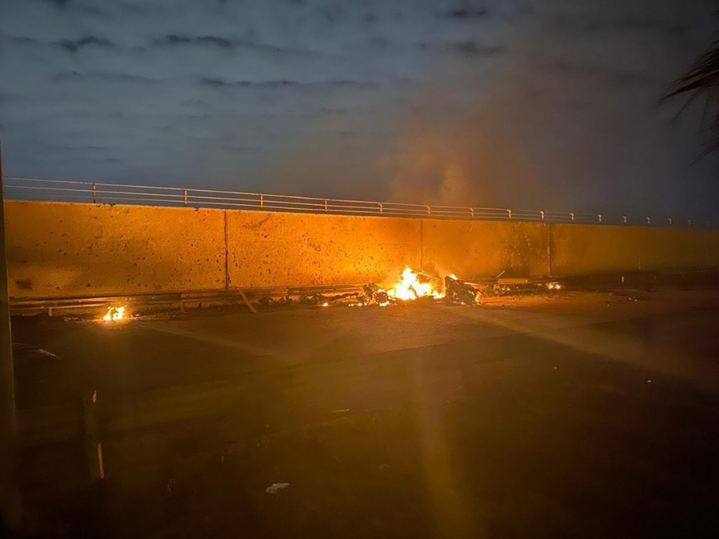 This photo released by the Iraqi Prime Minister Press Office shows a burning vehicle at the Baghdad International Airport following an airstrike, in B...
