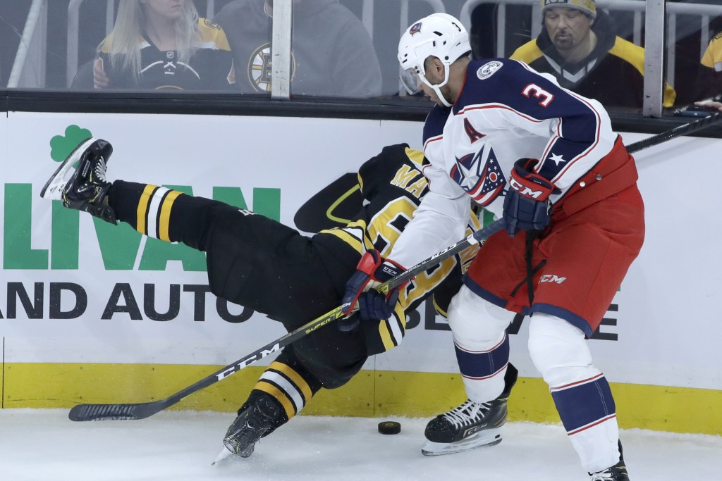 Columbus Blue Jackets defenseman Seth Jones (3) dumps Boston Bruins left wing Brad Marchand (63) to the ice as they compete for the puck in the first ...