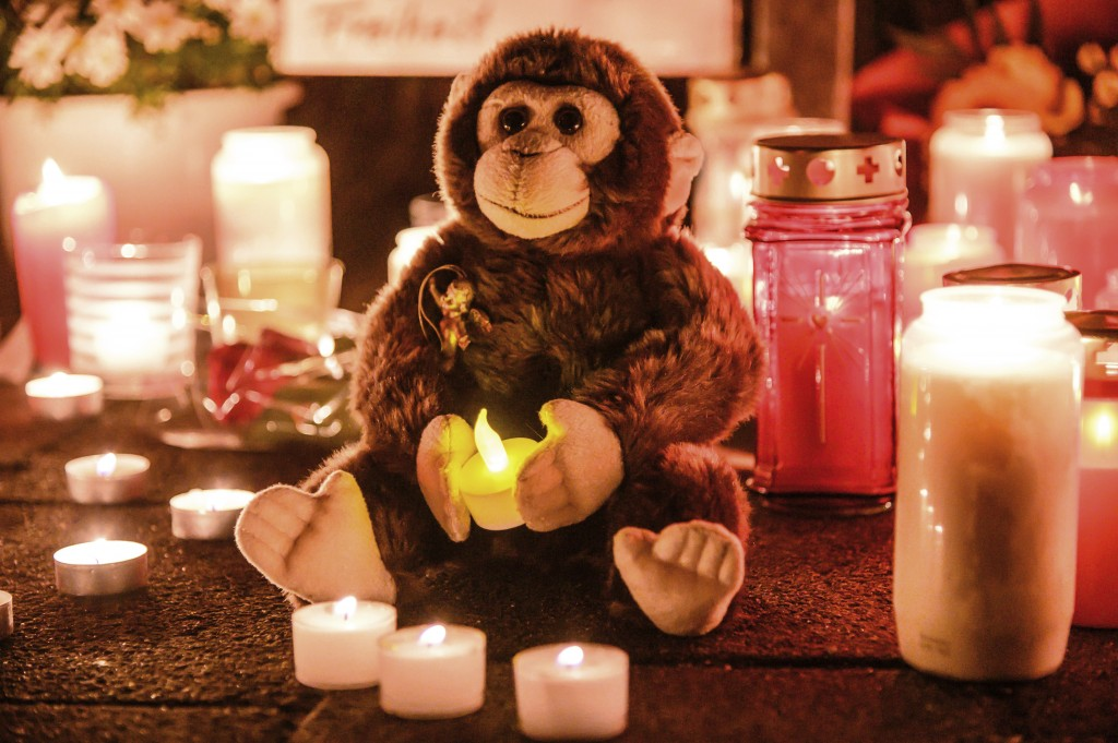 This Wednesday, Jan. 1, 2020 photo, a toy ape is placed between candles at the entrance of the Zoo in Krefeld, Germany. Three woman are under investig...