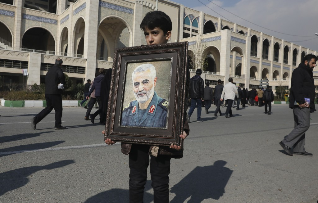 A boy carries a portrait of Iranian Revolutionary Guard Gen. Qassem Soleimani, who was killed in the U.S. airstrike in Iraq, prior to the Friday praye...
