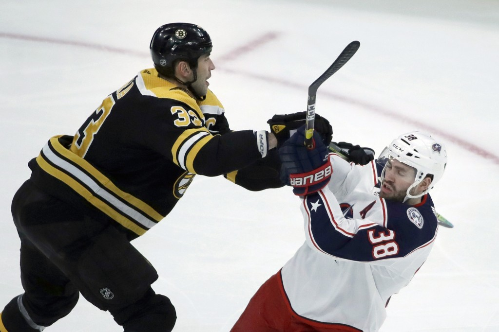 Boston Bruins defenseman Zdeno Chara (33) pushes off Columbus Blue Jackets center Boone Jenner (38) in the first period of an NHL hockey game, Thursda...