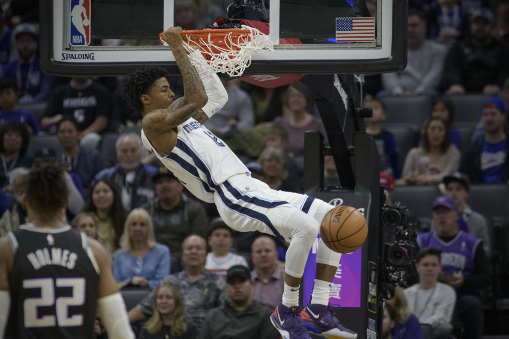 Memphis Grizzlies guard Ja Morant (12) dunks against the Sacramento Kings during the first quarter of an NBA basketball game in Sacramento, Calif., Th...