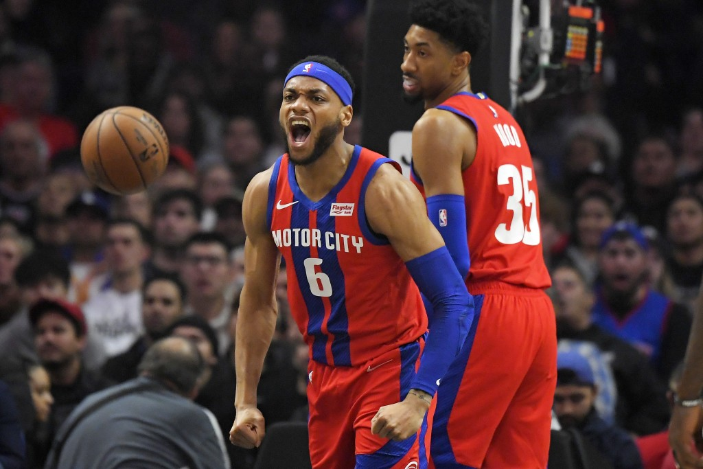 Detroit Pistons guard Bruce Brown, left, celebrates after scoring and drawing a foul as forward Christian Wood stands by during the first half of an N...
