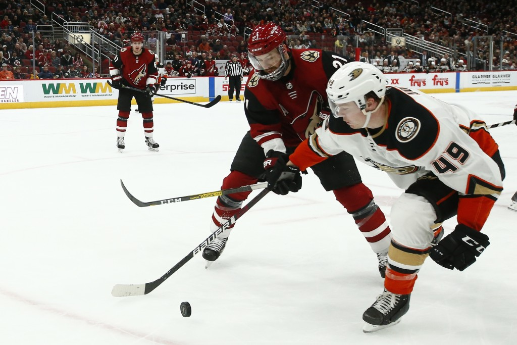 Anaheim Ducks left wing Max Jones (49) battles with Arizona Coyotes center Derek Stepan (21) for the puck as Coyotes left wing Lawson Crouse (67) look...