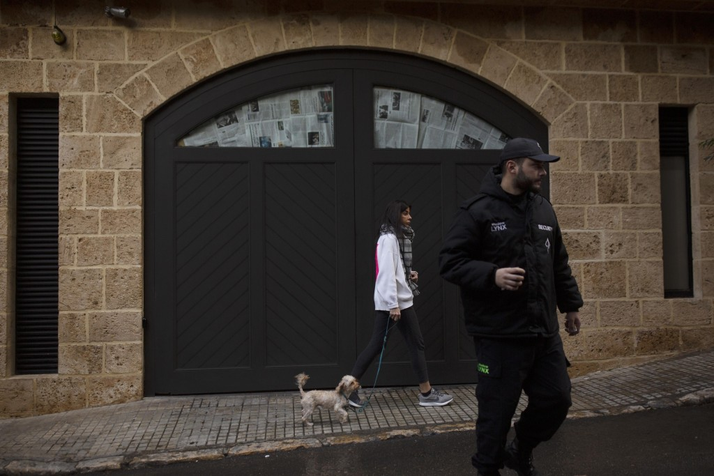 A private security guard stands nearby as a woman walks her dog past the house of ex-Nissan chief Carlos Ghosn in Beirut, Lebanon, Friday, Jan. 3, 202...