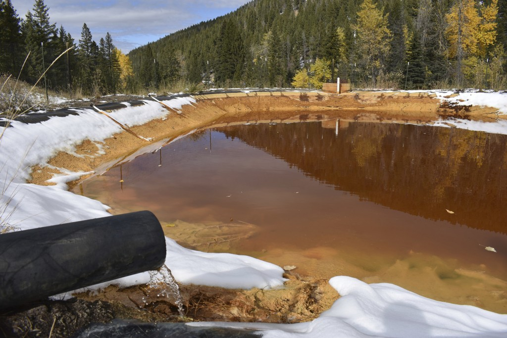 FILE - In this Oct. 12, 2018 file photo, water contaminated with arsenic, lead and zinc flows from a pipe out of the Lee Mountain mine and into a hold...
