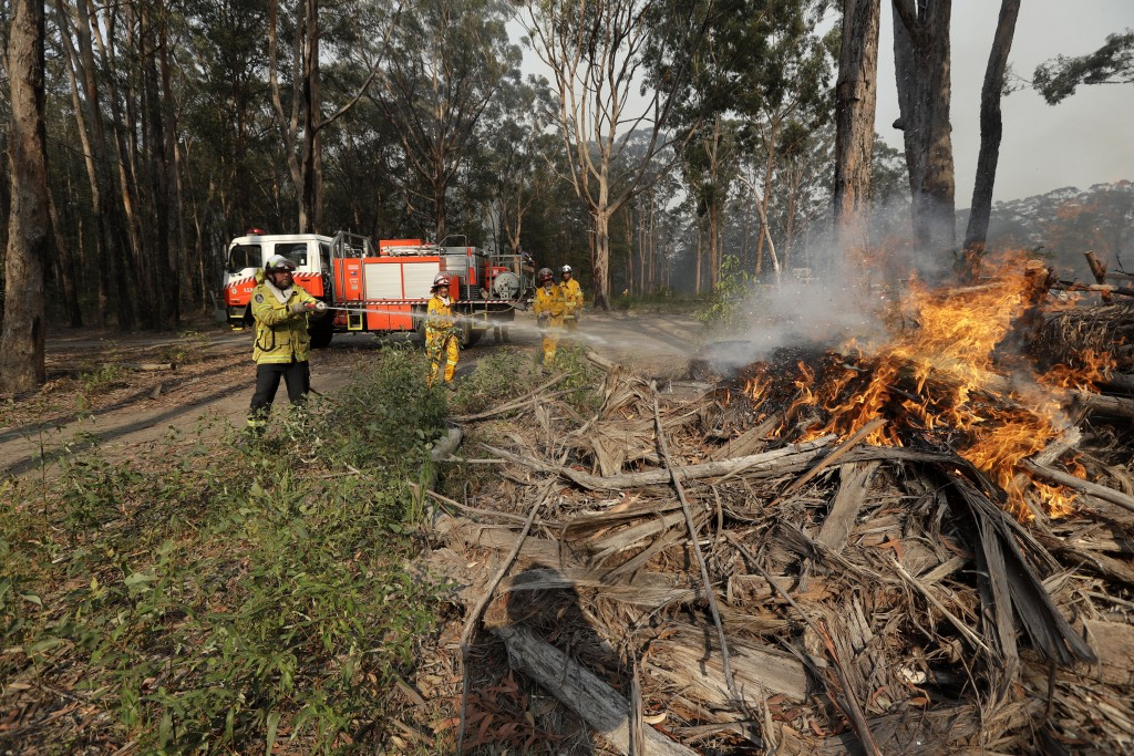 Firefighters battles a fire near Bendalong, Australia, Friday, Jan. 3, 2020. Navy ships plucked hundreds of people from beaches and tens of thousands ...