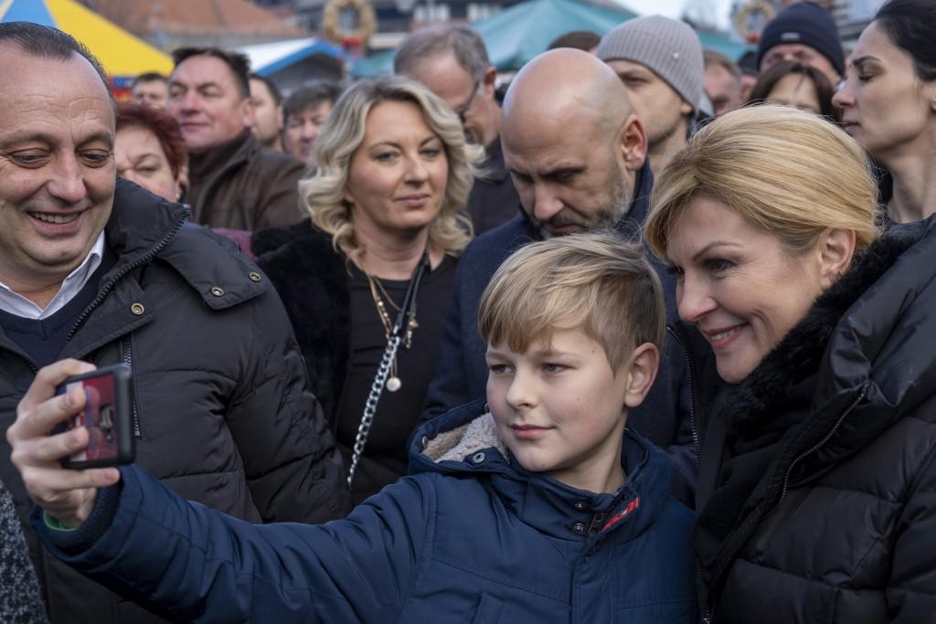 In this Dec. 31, 2019, photo, a boy takes photo with the incumbent president Kolinda Grabar Kitarovic at a rally in Marija Bistrica near Zagreb, Croat...