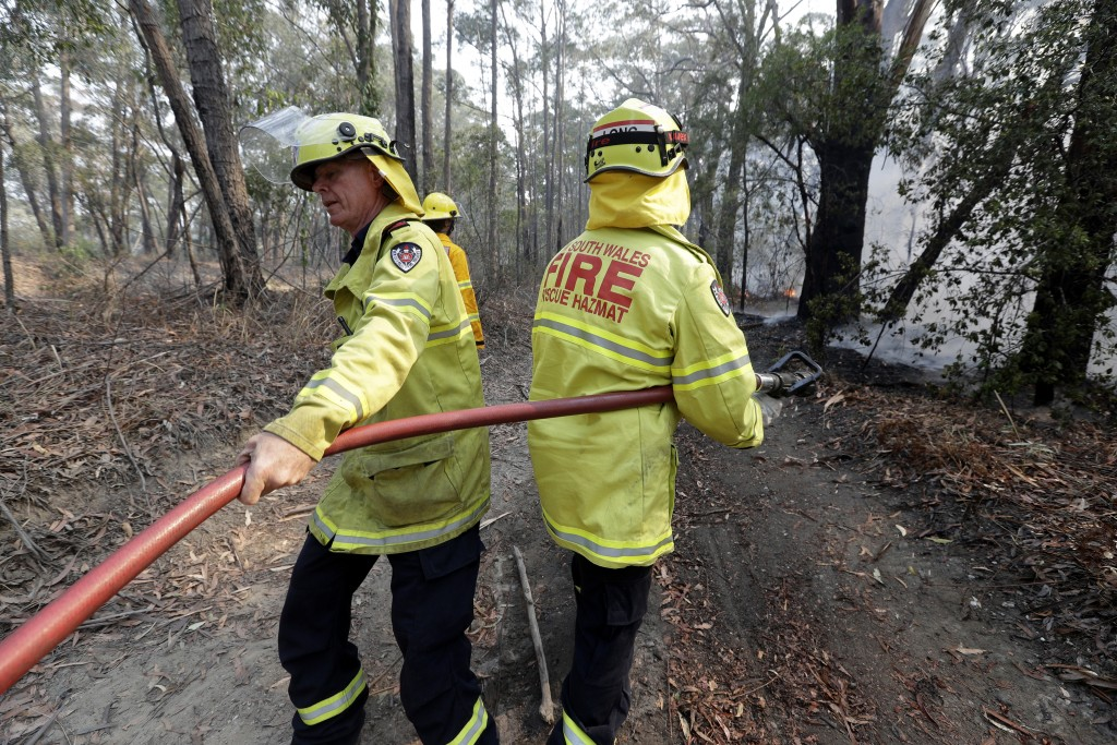 Firefighter battle a fire near Bendalong, Australia, Friday, Jan. 3, 2020. Navy ships plucked hundreds of people from beaches and tens of thousands we...