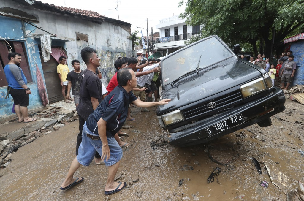 Residents move the wreckage of cars that were swept away by flood in Bekasi, West Java, Indonesia, Friday, Jan. 3, 2020.Severe flooding in greater Jak...