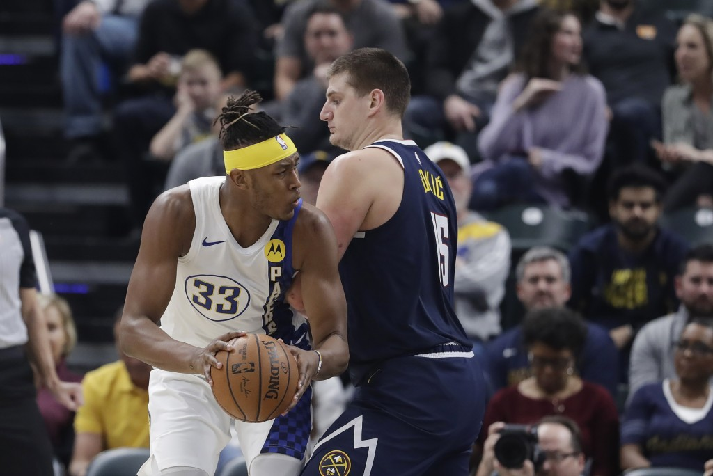 Indiana Pacers' Myles Turner (33) goes to the basket against Denver Nuggets' Nikola Jokic (15) during the first half of an NBA basketball game Thursda...