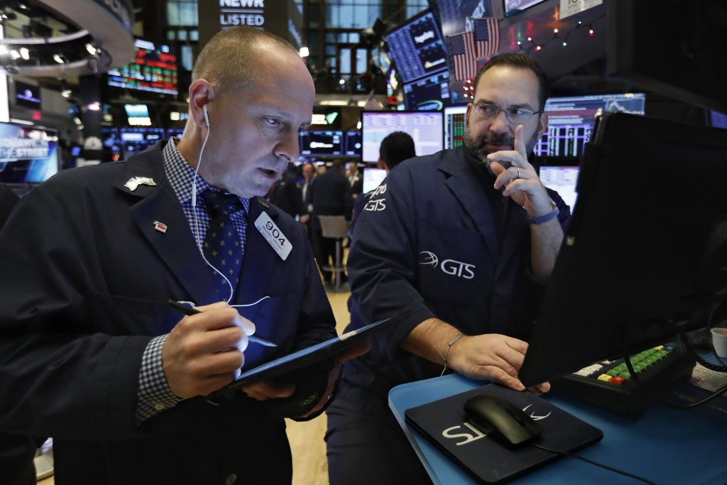FILE - In this Dec. 11, 2019, file photo trader Michael Urkonis, left, and specialist Anthony Matesic work on the floor of the New York Stock Exchange...