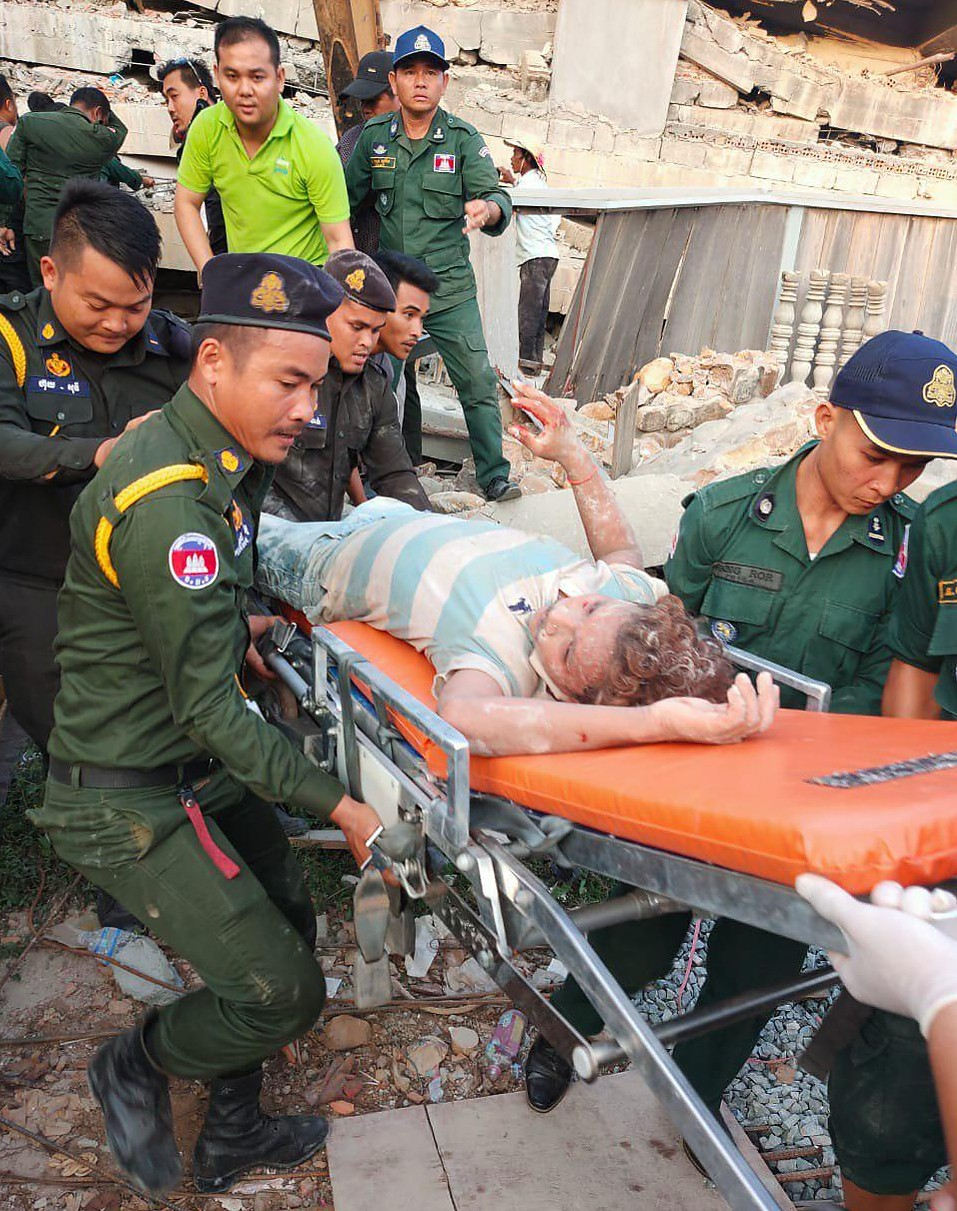 Photo provided by the Kep Province Authority Police, emergency workers carry a survivor from the debris after a building collapsed in Kep province, Ca...
