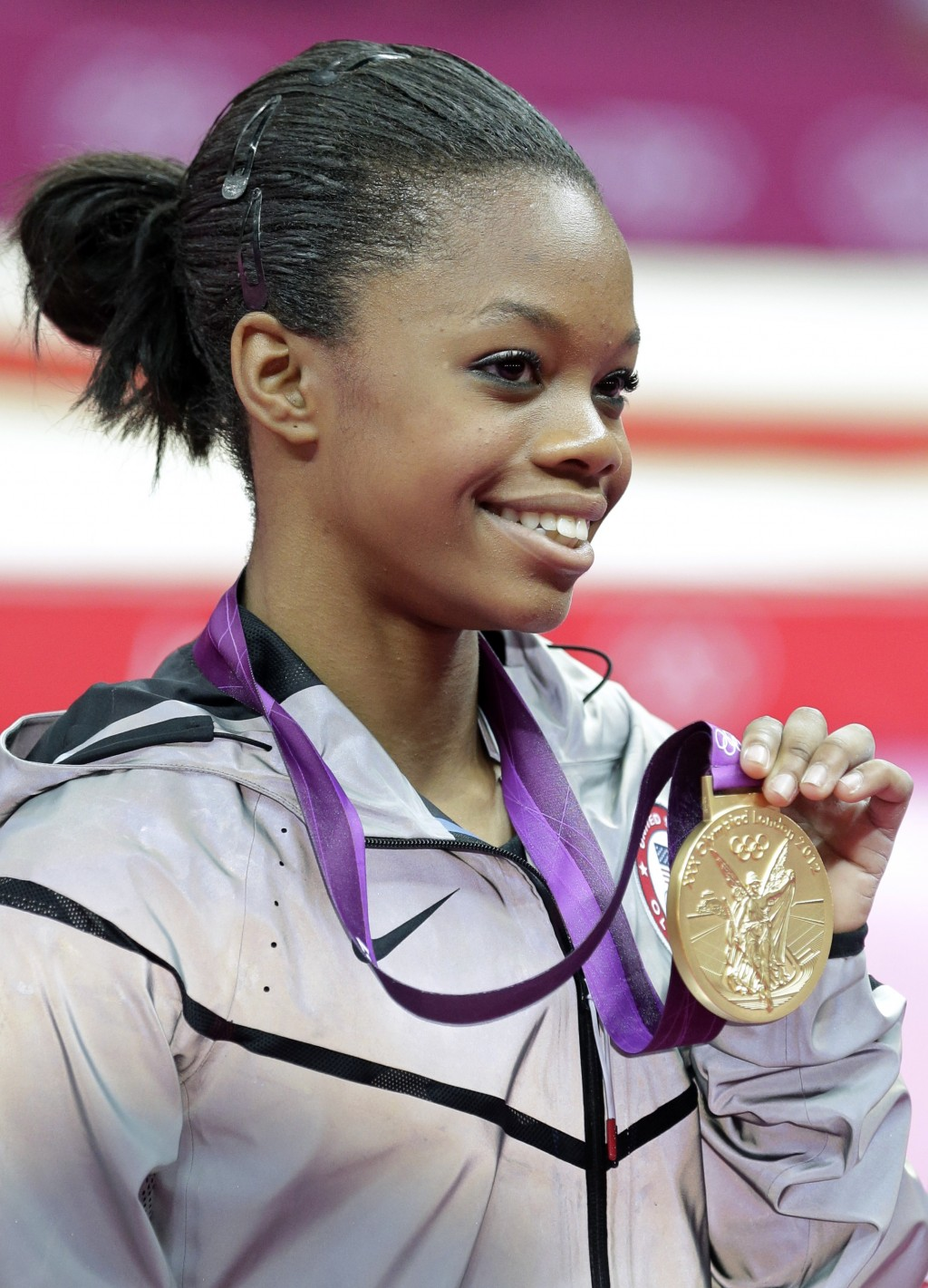 FILE - This Aug. 2, 2012 file photo shows U.S. gymnast Gabrielle Douglas displaying her gold medal during the artistic gymnastics women's individual a...
