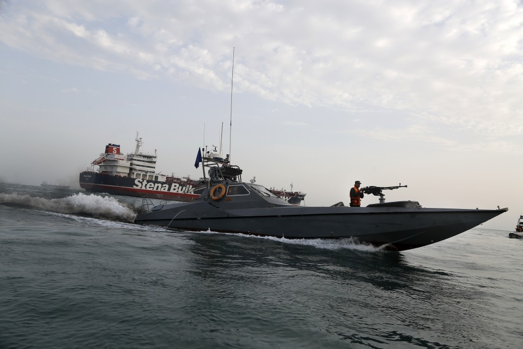 FILE - A speedboat of the Iran's Revolutionary Guard moves around a British-flagged oil tanker Stena Impero, which was seized on Friday by the Guard, ...