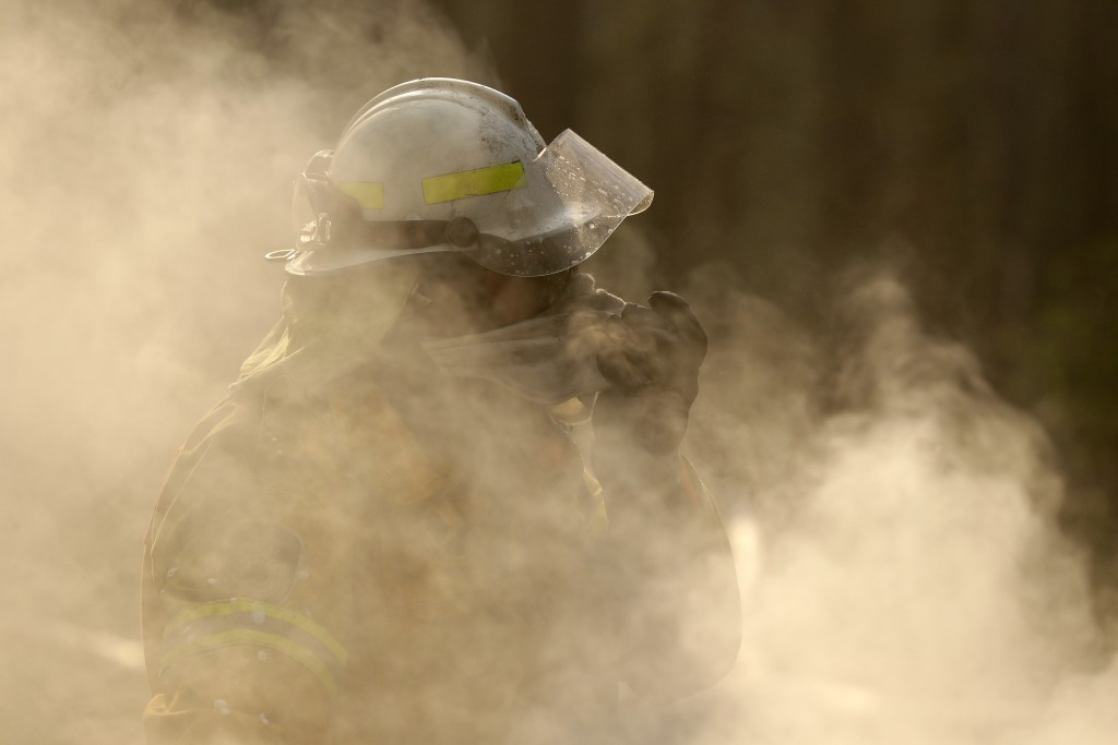 In this Friday, Jan. 3, 2020, file photo, a firefighter covers his face from block smoke as he battles a fire near Bendalong, Australia. (AP Photo/Ric...