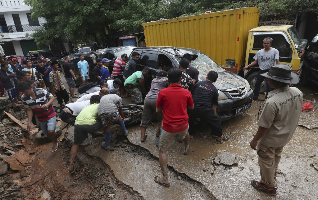 Residents try to move the wreckage of cars that were swept away by flood in Bekasi, West Java, Indonesia, Friday, Jan. 3, 2020.Severe flooding in grea...