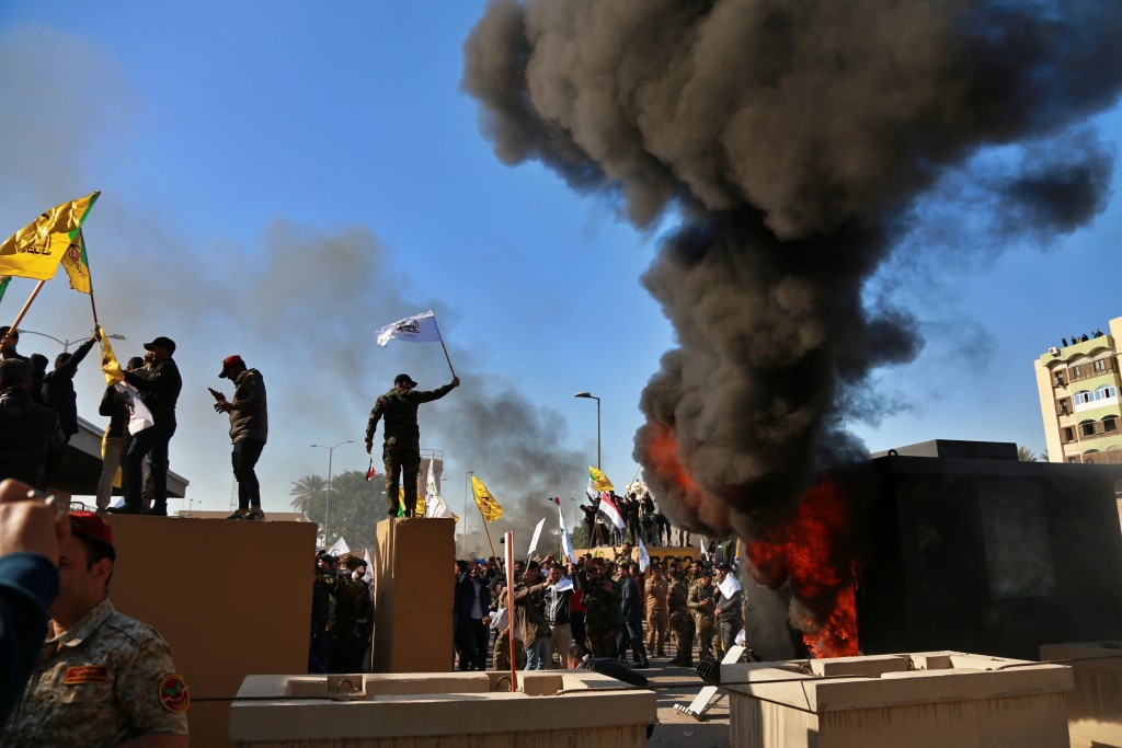 Protesters set fires in front of the U.S. embassy compound, in Baghdad, Iraq, Tuesday, Dec. 31, 2019. Dozens of angry Iraqi Shiite militia supporters ...