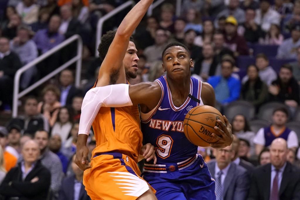 New York Knicks guard RJ Barrett (9) drives against Phoenix Suns guard Devin Booker in the first half of an NBA basketball game, Friday, Jan. 3, 2020,...