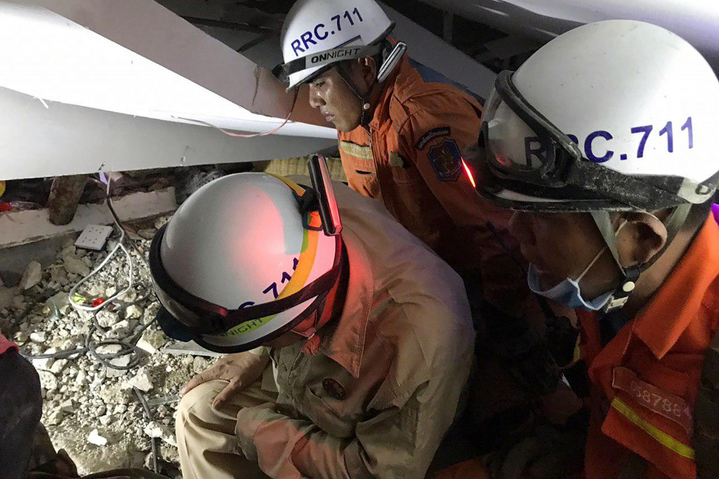 In this photo provided by the Kep Provincial Authority, emergency workers conduct a recovery operation inside a collapsed building in Kep province, so...