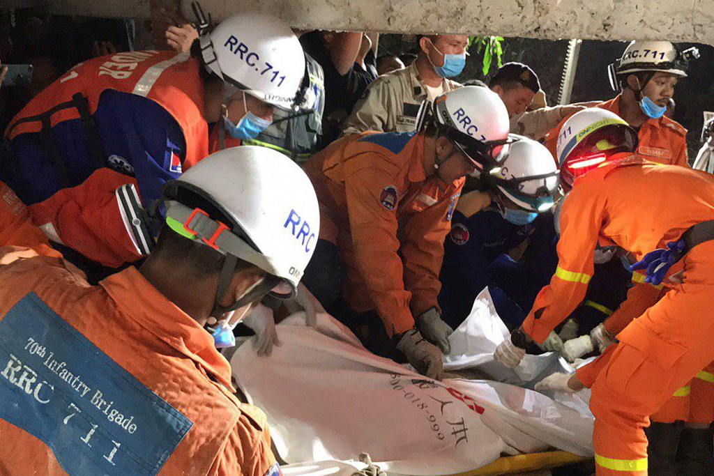 In this photo provided by the Kep Provincial Authority, emergency workers wrap the body of a victim of a building collapse in Kep province, southern C...