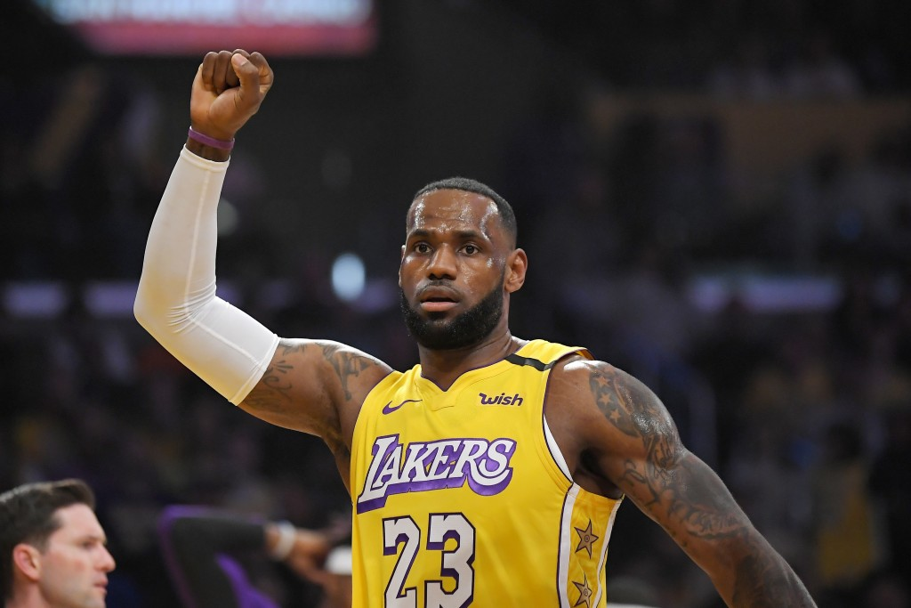 Los Angeles Lakers forward LeBron James celebrates after scoring during the first half of the team's NBA basketball game against the New Orleans Pelic...