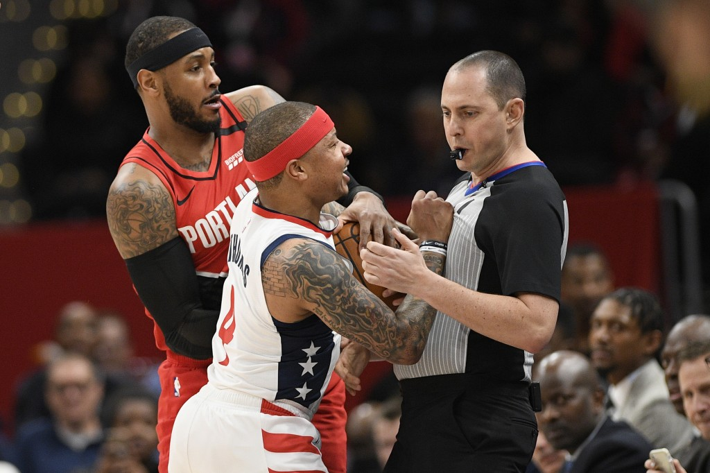 Washington Wizards guard Isaiah Thomas (4) comes in contact with referee Marat Kogut, right, next to Portland Trail Blazers forward Carmelo Anthony, b...