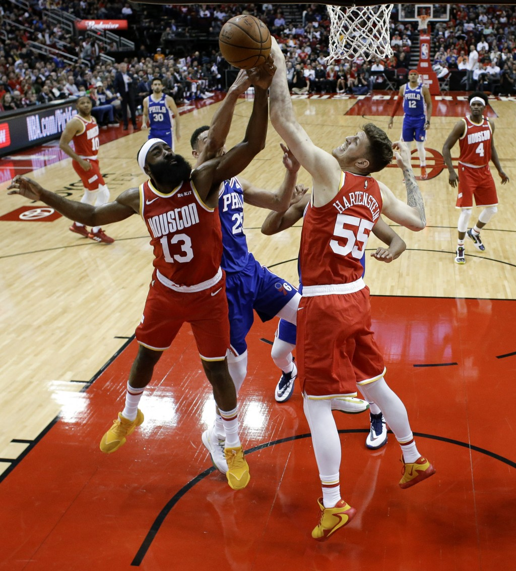 Houston Rockets center Isaiah Hartenstein (55) and guard James Harden (13) and Philadelphia 76ers guard Ben Simmons, center, vie for a rebound during ...