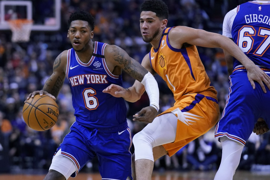 New York Knicks guard Elfrid Payton (6) drives against Phoenix Suns guard Devin Booker in the first half during an NBA basketball game, Friday, Jan. 3...