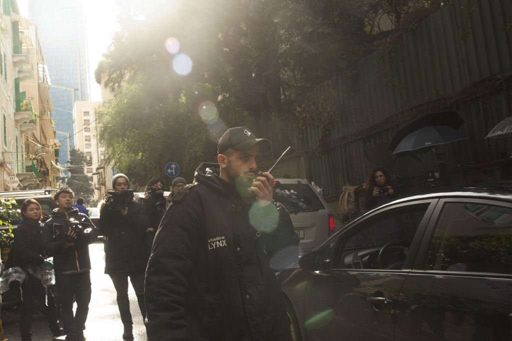 A private security guard speaks on a radio as a vehicle approaches the house of ex-Nissan chief Carlos Ghosn in Beirut, Lebanon, Saturday, Jan. 4, 202...