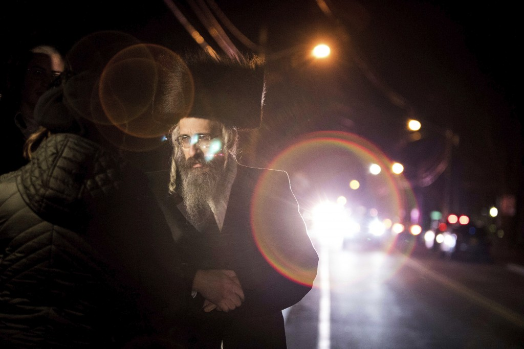 Orthodox Jewish people gather on a street in Monsey, N.Y., on early Sunday, Dec. 29, 2019, following a nearby stabbing late Saturday at a Hanukkah cel...