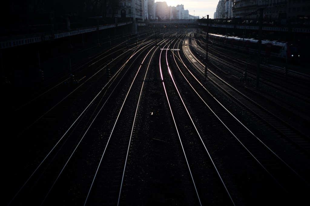 Light reflects from empty railway tracks outside the Saint Lazare train station in Paris on Tuesday, Dec. 31, 2019. The strikes over the French govern...
