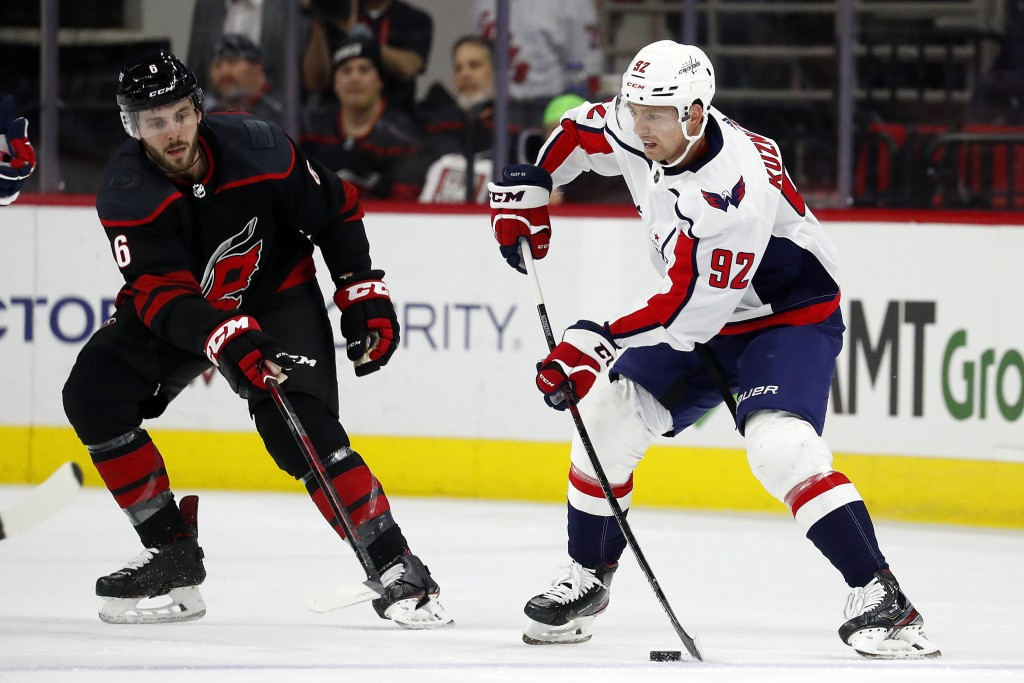 Washington Capitals' Evgeny Kuznetsov (92), of Russia, looks to pass the puck with Carolina Hurricanes' Joel Edmundson (6) nearby during the second pe...