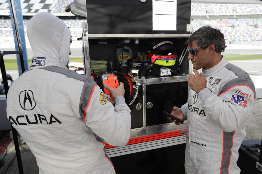 Dane Cameron, left, prepares to go out on the track after Juan Pablo Montoya, right, comes in for a break during testing for the upcoming Rolex 24 hou...
