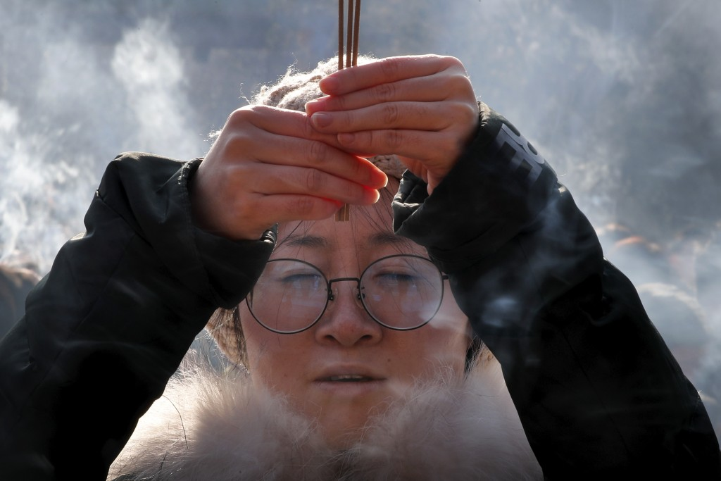 A woman holding incense sticks offers prayers on the first day of the New Year at Yonghegong Lama Temple in Beijing, Wednesday, Jan. 1, 2020. New Year...