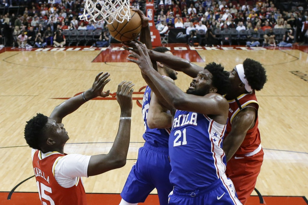 Philadelphia 76ers center Joel Embiid (21) and Houston Rockets forward Danuel House Jr., right, vie for a rebound during the first half of an NBA bask...