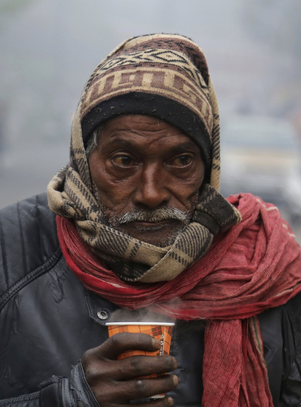 A man holds a hot cup of tea on a cold and foggy morning in Jammu, India, Tuesday, Dec. 31, 2019. Opaque, chilly smog has blanketed northern India as ...