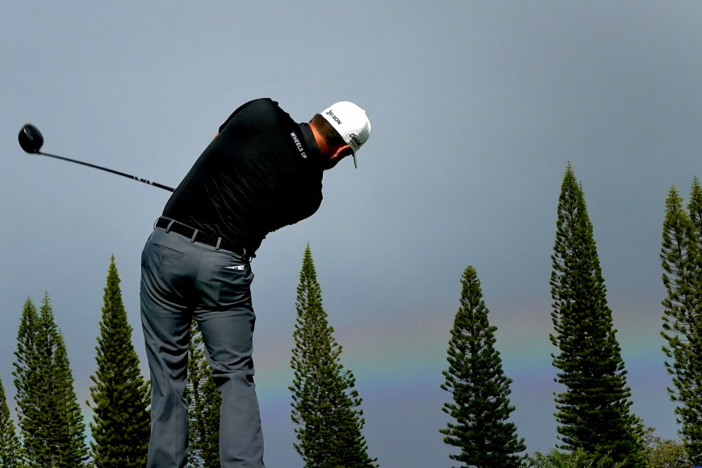 Graeme McDowell hits from the first tee as a rainbow forms on the horizon during second round of the Tournament of Champions golf event, Friday, Jan. ...