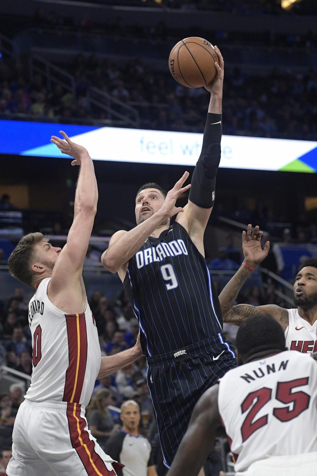 Orlando Magic center Nikola Vucevic (9) goes up to shoot between Miami Heat forward Meyers Leonard (0), guard Kendrick Nunn (25) and forward Derrick J...