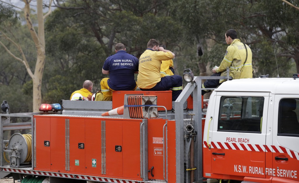 Firefighters at Batemans Bay, Australia, relax after a fire threat near their homes eased Saturday, Jan. 4, 2020. Australia's prime minister called up...