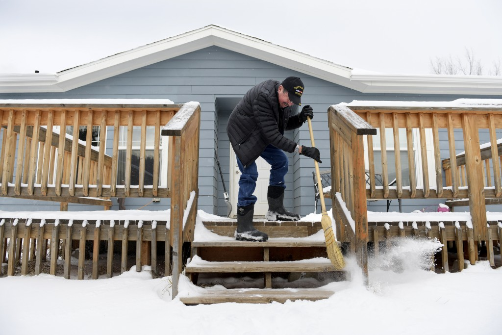 Richard King, 70, sweeps off the front steps to his home near Zortman, Mont., on the Fort Belknap Indian Reservation on Sunday, Dec. 8, 2019. King ret...