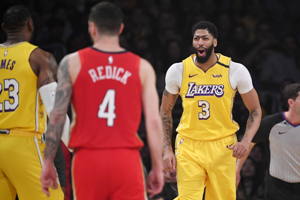 Los Angeles Lakers forward Anthony Davis, right, celebrates with forward LeBron James after dunking as New Orleans Pelicans guard JJ Redick looks away...